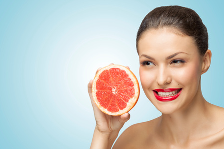 A creative portrait of a beautiful girl holding a red grapefruit sexually under her chin.