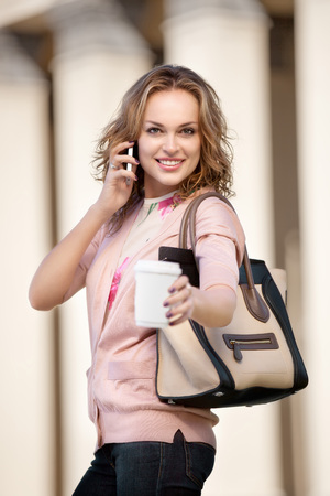 tea hot drink: A beautiful woman chatting via phone and offering a cup of take away coffee. Stock Photo