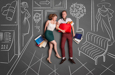 two: Love story concept of a romantic couple on shopping against chalk drawings background. Young happy couple standing together with shopping bags in a shopping mall. Stock Photo
