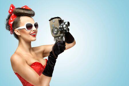 reportero: Una foto de la niña de pin-up en corsé y guantes de la celebración de la cosecha cámara de 8 mm.