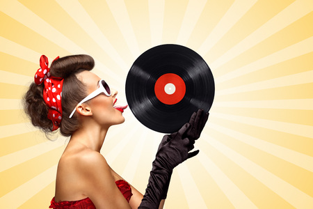 melomaniac: Vintage photo of glamorous pinup girl wearing long gloves, red ribbon in her hair and sunglasses, touching retro vinyl with her tongue on colorful abstract cartoon style background.