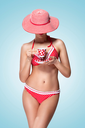 A vintage photo of a beautiful pin-up girl in bikini drinking tea and hiding head under a sun hat. Stock Photo