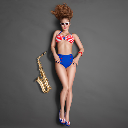 young woman nude: Top view of a beautiful pin-up girl in retro bikini and sunglasses, posing with a gold jazz saxophone on chalkboard background. Stock Photo