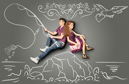 Happy valentines love story concept of a romantic couple sitting on an island and fishing a goldfish on a hook against chalk drawings background. Stok Fotoğraf