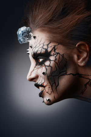 The pierced female face painted as a grinning halloween witch with a cracked paint and an ice cube.