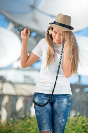 Happy young woman in hat listening to the music in vintage music headphones and dancing against background of satellite dishes that receive wireless signals from satellites. Stock Photo