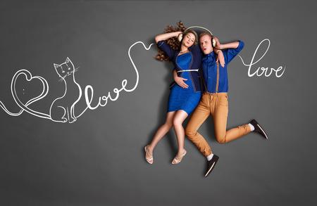 music lyrics: Concepto feliz de la historia de amor de las tarjetas del día de San Valentín de una pareja romántica que comparte los auriculares y que escucha la música sobre amor contra el fondo de los gráficos de la tiza de letras.