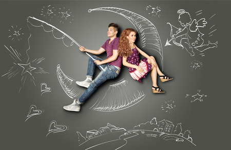 two: Happy valentines love story concept of a romantic couple fishing on a moon with a star on a hook against chalk drawings background of a night sky and a Cupid.