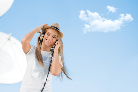 dish disk: Happy young woman in hat listening to the music in vintage music headphones and dancing against background of satellite dish that receives wireless signals from satellites.