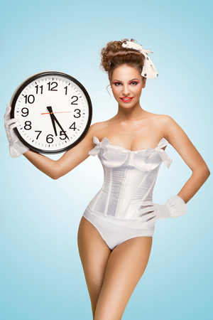 A cute pin-up girl with a vintage hairstyle holding an office wall clock and showing the time. Stock Photo