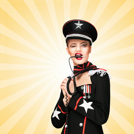 Sexy girl, dressed in a military uniform dress like a dominatrix, biting vintage unplugged music headphones on colorful abstract cartoon style background.
