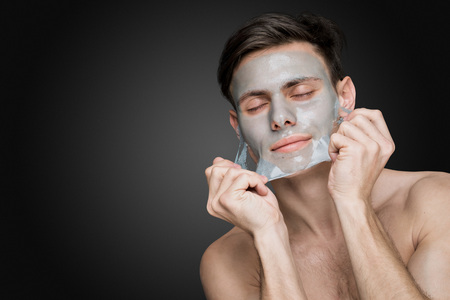 salon: Portrait of a beautiful young man peeling off a facial mask, face and body skin care retreat.
