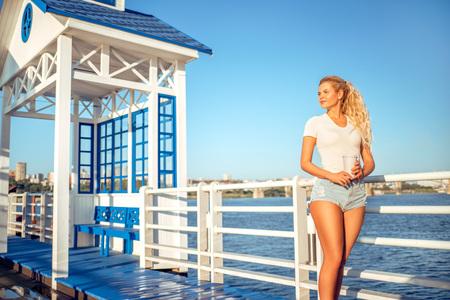 水の近くの橋の上に立って、離れてコーヒー カップを取ると美しい若い女性。