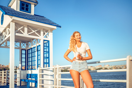 wharf: Beautiful young woman with a take away coffee cup, standing on the bridge near the water.