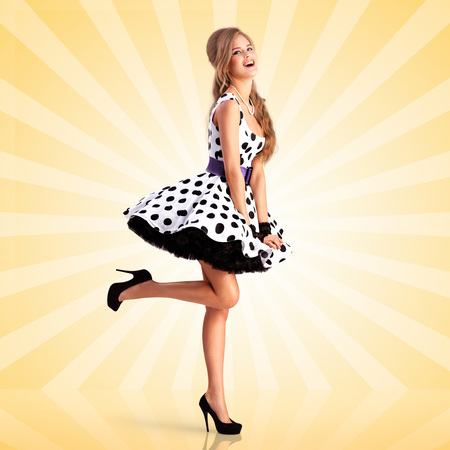 Creative vintage photo of a smiling pin-up girl wearing a retro polka-dot dress on colorful abstract cartoon style background.