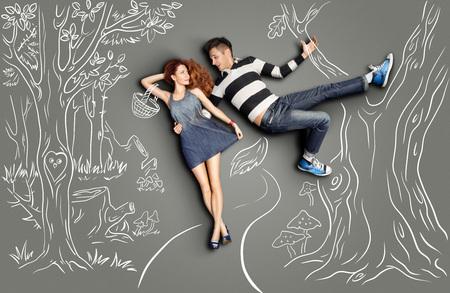 Gelukkige valentijns liefde verhaal concept van een romantisch paar lopen in het bos en flirten tegen krijt tekeningen natuur achtergrond. Mannelijk als een Grote Slechte Wolf die op een boom hangt en zijn vriendin knuffelt als een Rode Ruitkap.