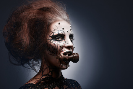 A creative photo of a queens painted pierced face holding a chess king in her mouth. Stock Photo