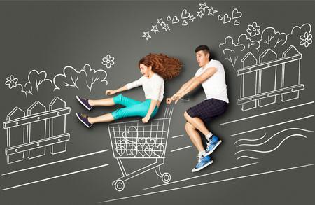 Happy valentines quiere concepto historia de una pareja romántica en dibujos de tiza de fondo. Masculino montando su novia en un carrito de la compra a lo largo de la calle. photo