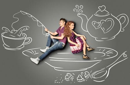 Happy valentines quiere concepto historia de una pareja romántica, sentado en un platillo y la pesca en un vaso de agua contra el fondo dibujos de tiza. photo