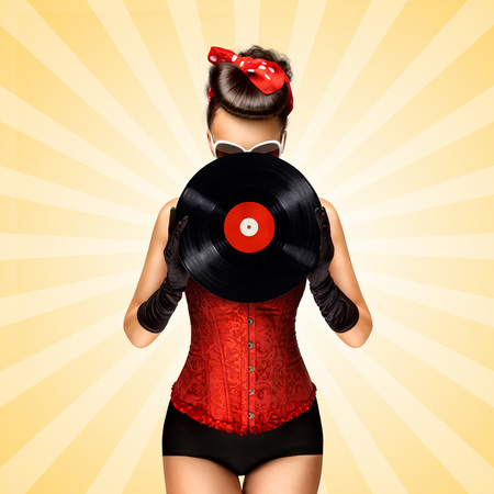 Vintage photo of glamorous pinup girl wearing long gloves and dressed in a red sexy corset, hiding behind LP vinyl record on colorful abstract cartoon style background.