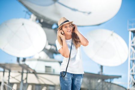 music background: Happy young woman in hat listening to the music in vintage music headphones and dancing against background of satellite dishes that receive wireless signals from satellites. Stock Photo
