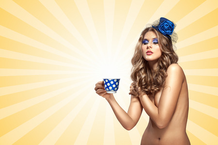 Creative vintage photo of a beautiful naked pin-up girl in a hat, drinking tea or coffee from a polka dot cup on colorful abstract cartoon style background.
