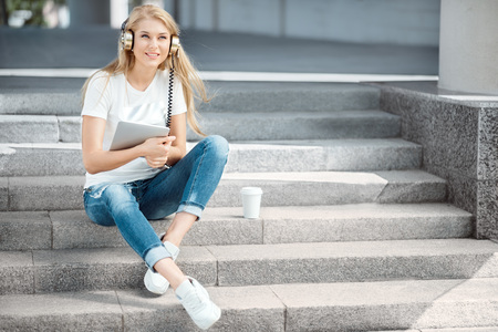 Happy young woman with vintage music headphones and a take away coffee cup, surfing internet on tablet pc, listening to the music and sitting on stairs against urban city background. Stock Photo