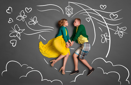 Happy valentines love story concept of a romantic couple sitting on the moon, holding hands and kissing against chalk drawings background of a night sky with butterflies. photo