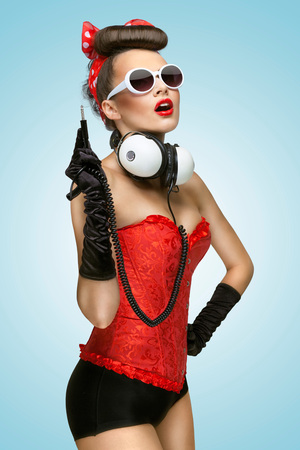 The pin-up photo of a cute girl in sunglasses with unplugged music headphones.