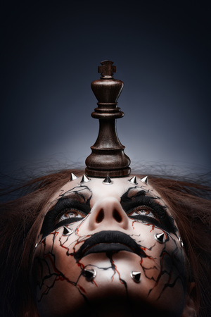 A creative photo of a queen with a painted pierced face and a chess king in her mouth.