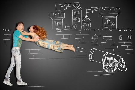 Happy valentines love story concept of a romantic couple against chalk drawings background. Male catching his girlfriend launched as a human cannonball. Imagens