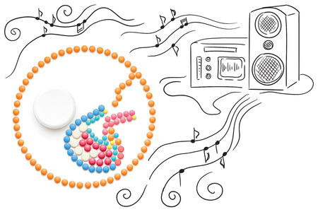 Creative medicine and healthcare concept made of pills, a baby listening to music, on sketchy background. Stock Photo