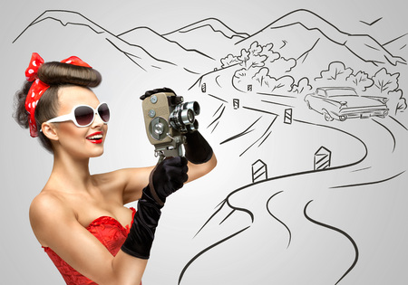 Glamorous pin-up girl filming nature and countryside with an old retro cinema 8 mm camera, standing in front of a road on grey sketchy background.