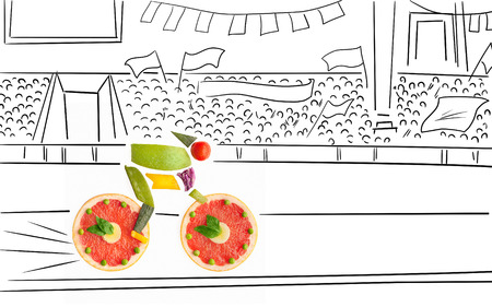 Fruits and vegetables in the shape of a cyclist riding a bike on a track.