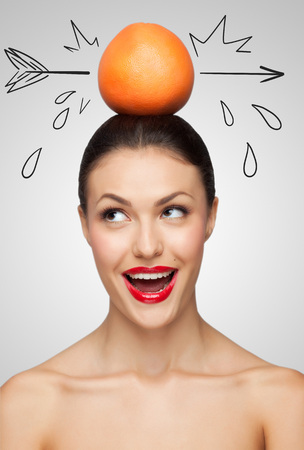 Creative portrait of a beautiful smiling woman holding a red grapefruit pierced with a sketchy arrow on her head.