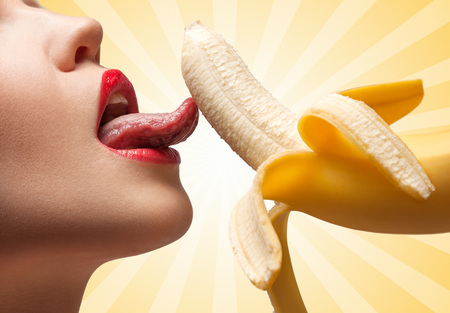 beautiful naked woman: A face of a hot girl that is licking a half-peeled yellow banana on colorful abstract cartoon style background.