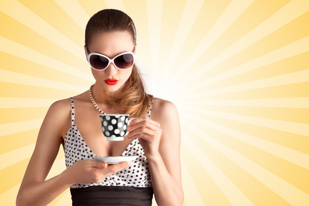 Creative vintage photo of a beautiful pin-up girl in a polka dot bikini and sunglasses, drinking tea or coffee on colorful abstract cartoon style background.