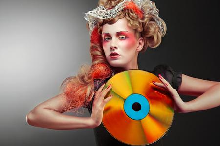 복고풍 레이저 디스크를 들고 매혹적인 빈티지 여자.
