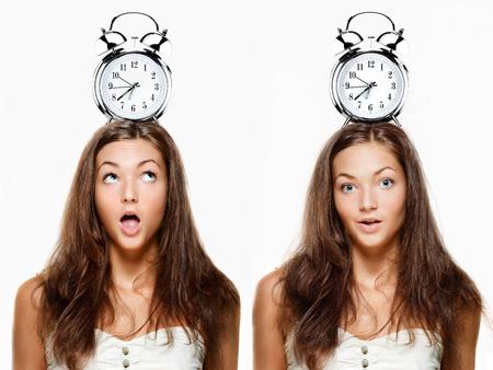 朝は遅刻、レトロな目覚まし時計彼女の頭の上に保持している若い女性の写真を設定します。 写真素材