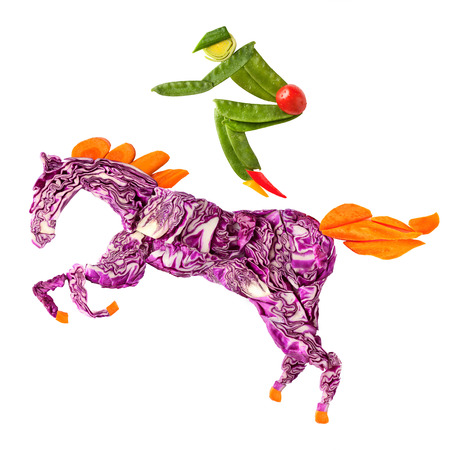 A food concept of a horse rider made of fruits and vegs isolated on white.