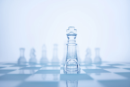 Photo of chess king standing in front of the same colour set in bright background.