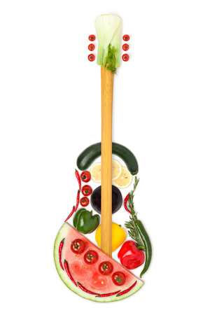 A colourful photo of the guitar made of fruits and vegetables.
