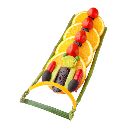 bobsled: Fruits and vegetables in the shape of a four-man bobsleigh team in a gravity-powered sled. Stock Photo