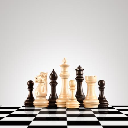 Koncepcja strategii i przywództwa; czarno-białe drewniane figury szachowe stojące na planszy gotowe do gry.