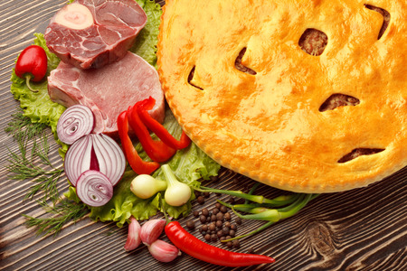 A colorful photo of traditional delicious beef osetinian pie. Fydzhin meat pie and vegetables on wood.