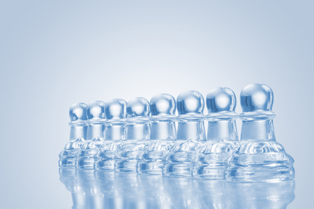 A raw of transparent glass pawns on reflective surface. Stock Photo