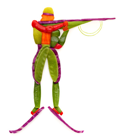 Fruits and vegetables in the shape of a biathlete with a rifle in a standing position.