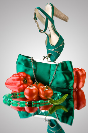 A close-up of a blue purse, high-heeled shoe, beads and vegetables. Stock Photo