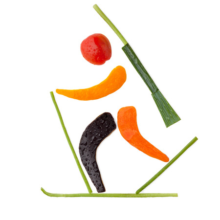 Fruits and vegetables in the shape of a biathlete skiing a final lap after a penalty loop.