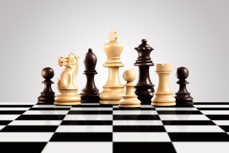 Strategy and leadership concept; black and white wooden chess figures standing on the board ready for game. Stock Photo